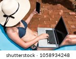 Portrait Beautiful Woman Sitting in deck chair and using laptop computer near swimming pool in vacation time blue water