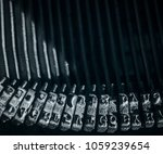 Small photo of Close-up on type hammers with roman alphabet letters of an old and dusty typewriter.
