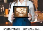 Small photo of Close up woman barista holding tablet and show bitcoin accepted here on tablet screen at cafe counter bar,seller coffee shop accept payment by crypto currency.digital money concept.modern waitress