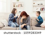 Stock photo kids having quarrel over tired mother mom is depressed by screaming of children problems of 1059283349