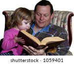 Father reading a story to toddler daughter isolated on white - stock photo