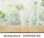 Small photo of Empty wood table top and blurred of interior room with window view green from tree garden background background - can used for display or montage your products.