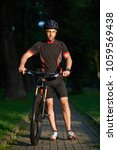 Small photo of Sporty smiling man bicyclist walking near bicycle happy to begin morning with training. Sportsman having fun exercising outdoors. Concept of healthy lifestyle, new beginning