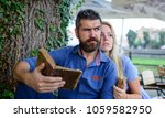 Small photo of Oldfashioned date concept. Girl with pensive face fall in love with bearded man, couple reads poems. Romantic couple holds old books with poems. Couple in love sit outdoor, nature background.