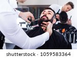 Small photo of Young satisfied male hairdresser accurately cutting beard of client at hair salon