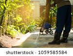 worker cleaning pathway with... | Shutterstock . vector #1059585584