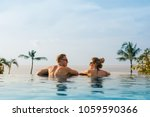 happy couple in infinity pool | Shutterstock . vector #1059590366