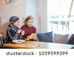 two young muslim women in cafe  ...   Shutterstock . vector #1059599399