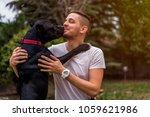 pit bull dog kissing his owner... | Shutterstock . vector #1059621986
