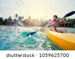 Young Man Paddling The Sea...