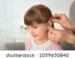 doctor putting hearing aid in... | Shutterstock . vector #1059650840