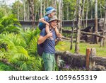 father and son at the zoo.... | Shutterstock . vector #1059655319