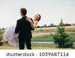 bridegroom carrying his bride... | Shutterstock . vector #1059687116