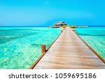a wooden bridge leading to a... | Shutterstock . vector #1059695186