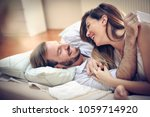 happy young couple in bed.... | Shutterstock . vector #1059714920