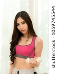 Small photo of Beautiful women wearing pink exercise clothes. Hold a white drumbeat glad to exercise for a healthy and strong body. Health concept