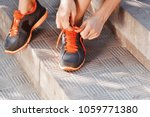 woman tying laces of running... | Shutterstock . vector #1059771380