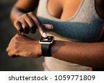 a woman wearing a smartwatch | Shutterstock . vector #1059771809