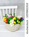 Small photo of Florist at work: How to make simple Easter table decoration with freesias, buxus, hay and eggs in ceramic bowl. Step by step, tutorial.