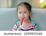 little asian child girl feeding ... | Shutterstock . vector #1059853160
