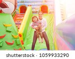 mom and child jumping in an... | Shutterstock . vector #1059933290