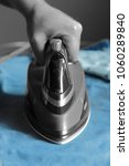 Small photo of Man ironing jeans with an electric iron with selective color
