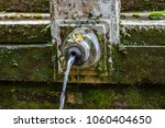water spout with canang sari at ... | Shutterstock . vector #1060404650