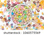Stock photo bowl of cereals and marshmallows and cereals scattered around the table on white background top 1060575569