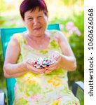 Small photo of Elderly happy patient holding daily dosage of expensive drugs.