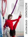 Small photo of Elegant gymnast doing stretching with barre in a studio