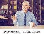 happy senior businessman giving ... | Shutterstock . vector #1060783106