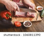 man cutting rack of lamb on... | Shutterstock . vector #1060811390