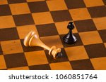 Small photo of The winner is the pawn and the defeated king on the chessboard. Chess. Competition and victory concept.