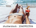 woman holds a cocktail  while... | Shutterstock . vector #1060902506