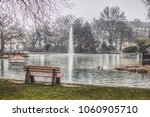a bench in front of lake with ducks swimming and a water fountain in the background. The photograph was taken in the public Parc de Merl in Luxembourg city.