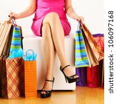 Small photo of Woman's legs and shopping bags