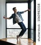 Small photo of Guy teenager in stylish clothes dances at window in studio of dance. Modern dance. Hip-hop movement.