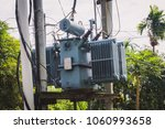 Small photo of Power transformers attached pole convert three phase power to 220V and 110V at 60 Hertz.