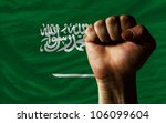 complete national flag of saudi arabia covers whole frame, waved, crunched and very natural looking. In front plan is clenched fist symbolizing determination - stock photo
