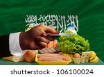 man stretching out credit card to buy food in front of complete wavy national flag of saudi arabia - stock photo
