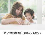 asian mother and her son... | Shutterstock . vector #1061012939