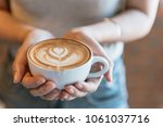 female hands holding a cup of... | Shutterstock . vector #1061037716