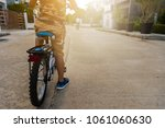 kid riding a bicycle on a... | Shutterstock . vector #1061060630