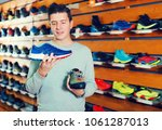 ordinary man chooses shoes in a ... | Shutterstock . vector #1061287013