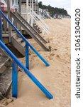 beach hut steps disappearing... | Shutterstock . vector #1061304020