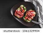 Small photo of Whole grain bread sandwiches with prosciutto, avocado, cucumber, tomatoes, herbs and seeds in plate on black stone background. Clean eating, healthy breakfast. Top view, flat lay