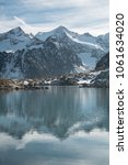 Small photo of Reflection of mountain peaks in a lake, Rinnensee, Stubaier Alpen, Austria