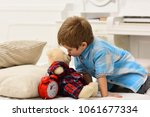 Small photo of Child in bedroom kiss toy in nose. Good night concept. Boy with happy face puts favourite toy on bed, wishing sweet dreams. Kid put plush bear near pillows and alarm clock, luxury interior background.