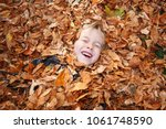 young child laying buried in a... | Shutterstock . vector #1061748590
