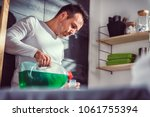 man wearing white shirt pouring ... | Shutterstock . vector #1061755394